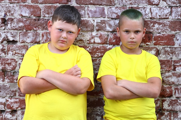 Due ragazzi in magliette gialle stanno a braccio incrociato contro un muro di mattoni. foto di alta qualità