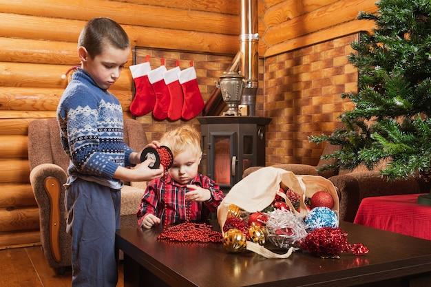 Due fratelli stanno aiutando a decorare l'albero di natale con perline rosse