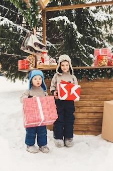 Due fratelli ragazzi con scatole regalo al mercatino di natale candy shop all'aperto
