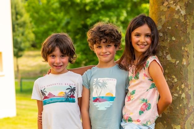 Due fratelli e una sorella sorridono in un parco vicino a un albero