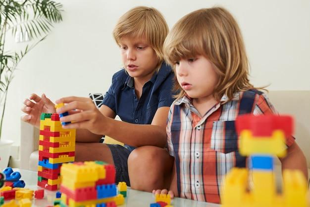 Due fratelli che giocano con i blocchi di plastica