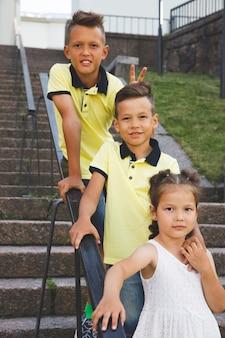 Due fratelli e una sorella sono in piedi sulle scale.