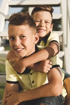 Due fratelli in magliette gialle si abbracciano sulle scale.