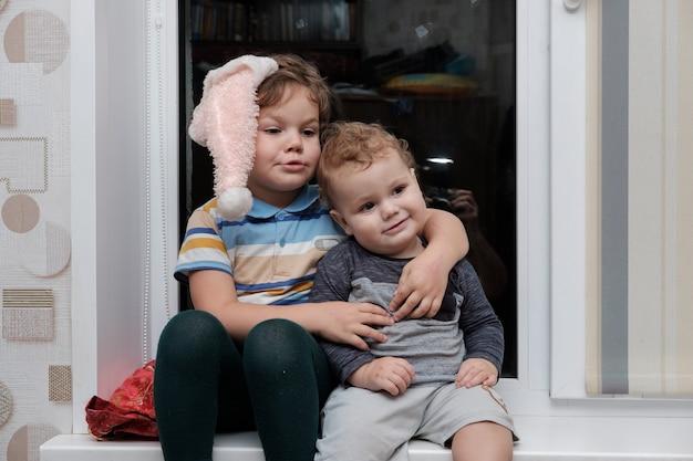 Due fratelli di giovane età seduti sul davanzale
