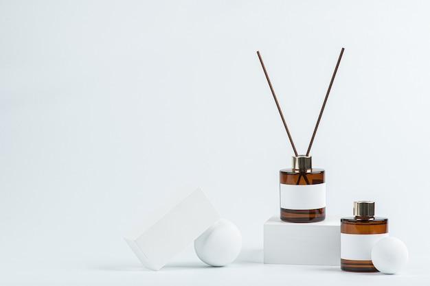 Due fiale di deodorante per ambienti marroni sono posizionate tra oggetti di scena bianchi