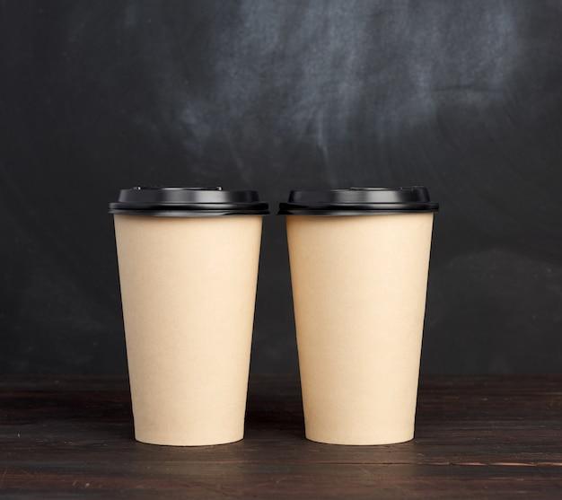 Due tazze usa e getta di carta marrone con un coperchio di plastica su un tavolo di legno