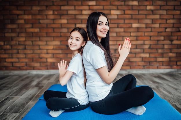 Due sorelle brune e in forma sedute schiena contro schiena in palestra e praticano yoga.