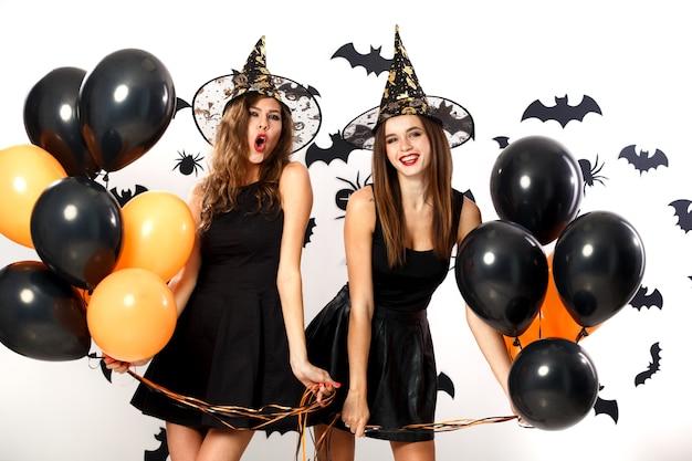 Due donne castane in abiti neri e cappelli da strega tengono palloncini neri e arancioni sullo sfondo del muro con pipistrelli. festa di halloween .