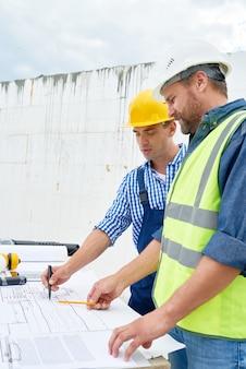Due costruttori che esaminano le planimetrie