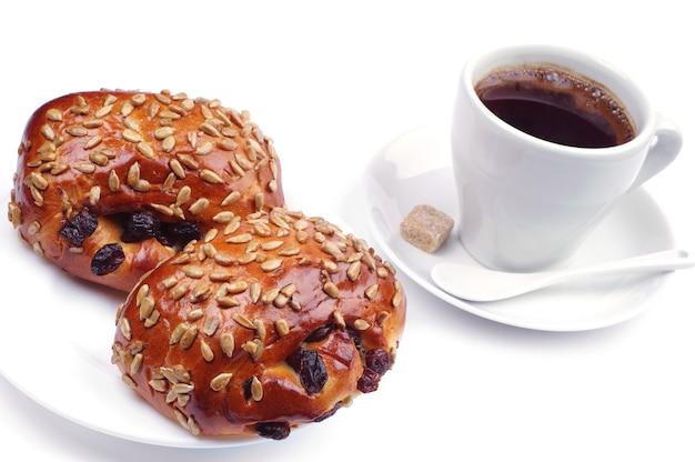 Due panini uvetta e semi di girasole con caffè su sfondo bianco