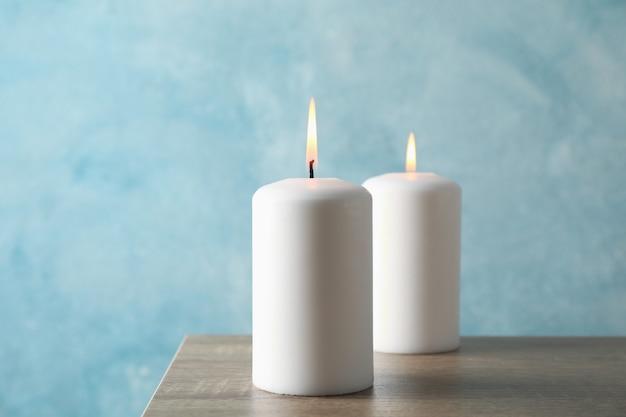 Due candele brucianti sulla tavola grigia contro il blu
