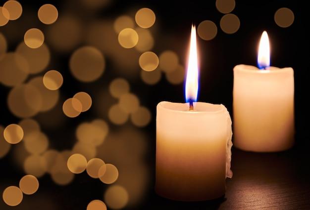 Due candele accese sul tavolo nel buio della notte. luci di candela al buio ed effetti di luce bokeh per momenti solenni e vacanze. vista ravvicinata con copia spazio.