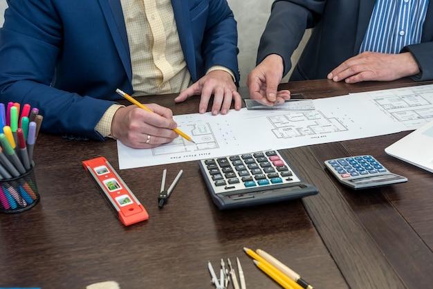 Due busimessman che lavorano con il piano architettonico della casa alla scrivania in ufficio. lavoro di squadra sul progetto Foto Premium