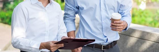 Due colleghi di lavoro che hanno discussione nuovo progetto riunione d'affari fuori ufficio in un ambiente urbano.
