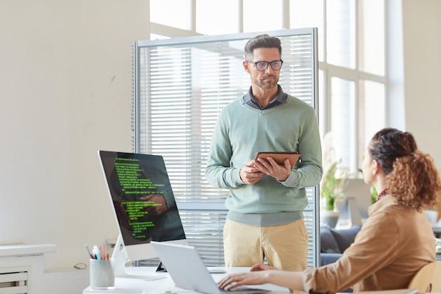 Due colleghi di lavoro che utilizzano tavoletta digitale e computer nel loro lavoro in ufficio