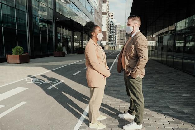 Due colleghi di lavoro che indossano maschere protettive parlano tra loro si incontrano in città
