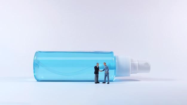 Figura dell'uomo di due affari che si leva in piedi davanti alla bottiglia dello spruzzo dell'alcool. concetto covid-19.