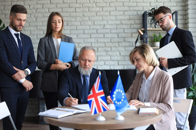 Due soci in affari che firmano un documento. l'unione europea il regno unito.