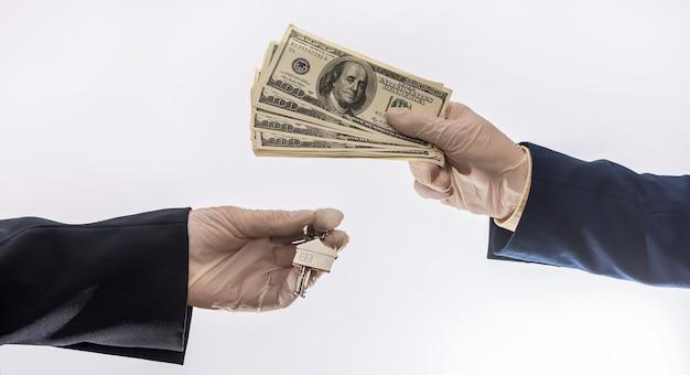 Due uomini d'affari eseguono un contratto di acquisto o locazione di una casa scambiando dollari e chiavi dell'appartamento. vendita casa