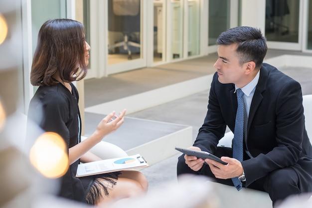 Due uomini d'affari che discutono e parlano in ufficio.