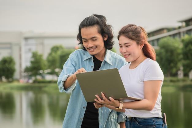 Due uomini d'affari felici di utilizzare la tecnologia informatica all'aperto