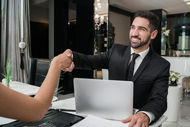 Due uomini d'affari che hanno la riunione e si stringono la mano