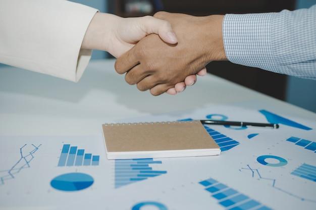Due uomini d'affari della stretta di mano dell'investitore trattano con il partner dopo aver terminato la riunione di lavoro