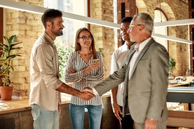 Due uomini d'affari che si stringono la mano e sorridono mentre sono in piedi con i colleghi nell'ufficio creativo