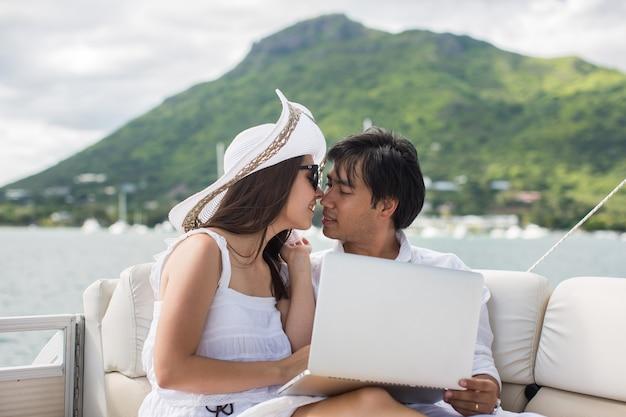 Due uomini d'affari che lavorano con il computer portatile su una barca a vela. viaggio in barca.