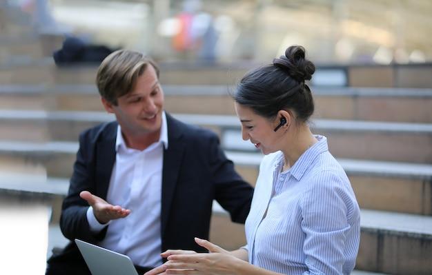 Due persone di affari che discutono mentre sedendosi all'ufficio esterno.