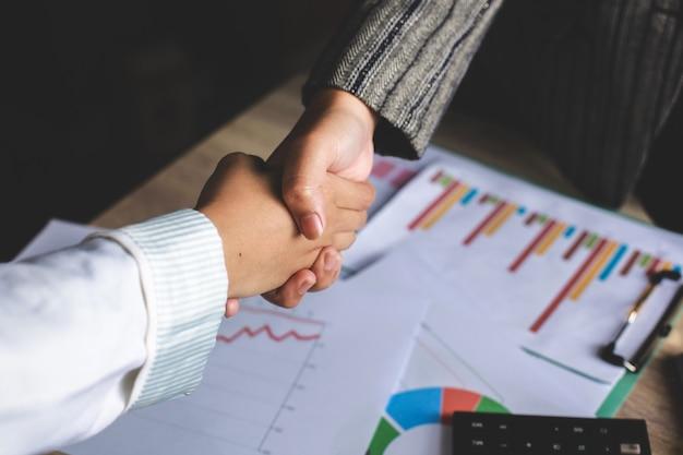 Due donna d'affari stringe la mano in ufficio