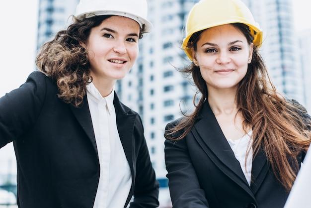 Due donne d'affari in caschi protettivi e occhiali di protezione che esaminano gli schemi di costruzione, concetto architettonico