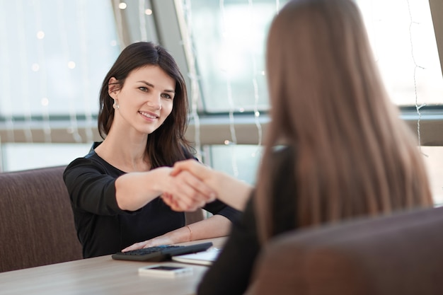 Due donne d'affari si stringono la mano in una riunione informale