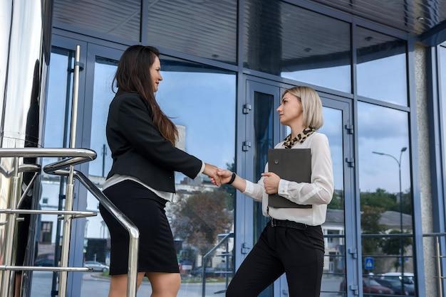 Due donne d'affari in giacca e cravatta handshake prima dell'edificio per uffici