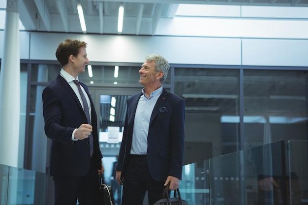 Due uomini d'affari che interagiscono tra loro nel corridoio