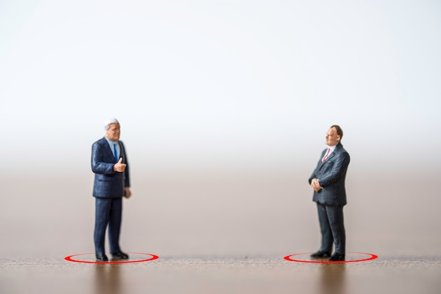 Il manager di due uomini d'affari in piedi e la discussione mantengono il distanziamento sociale per prevenire l'infezione da pandemia di diffusione di virus corona covid-19. concetto di allontanamento sociale.