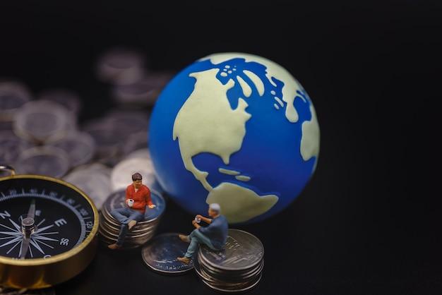 Figura in miniatura di due uomini d'affari seduta su una pila di monete d'argento con sfera mondiale e bussola