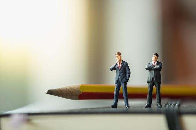 Figure miniatura di due uomini d'affari in piedi sul taccuino nero con la matita.