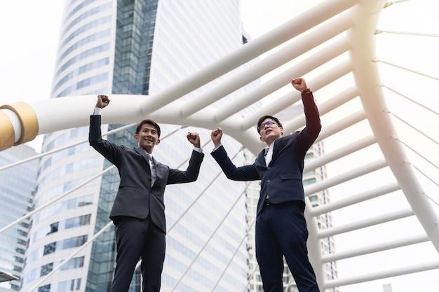 Due uomini d'affari che raggiungono obiettivi
