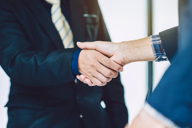 Due uomini d'affari che agitano le mani che si salutano.
