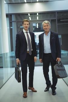 Due uomini d'affari in piedi in corridoio