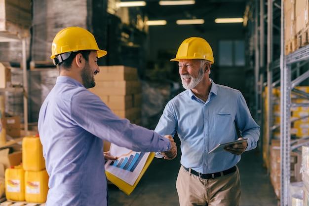 Uomo d'affari due con i caschi sulle teste che stringono le mani per il buon lavoro finito. interno di stoccaggio.