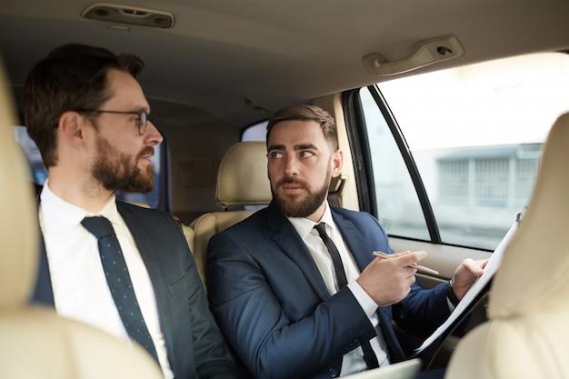 Due uomini d'affari che discutono di lavoro in macchina