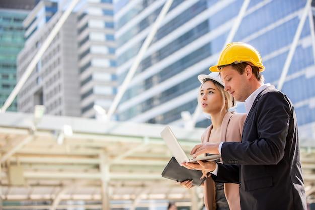 Conversazione e stretta di mano d'uso di due giubbotti di sicurezza della femmina e di uomini d'affari sul cantiere