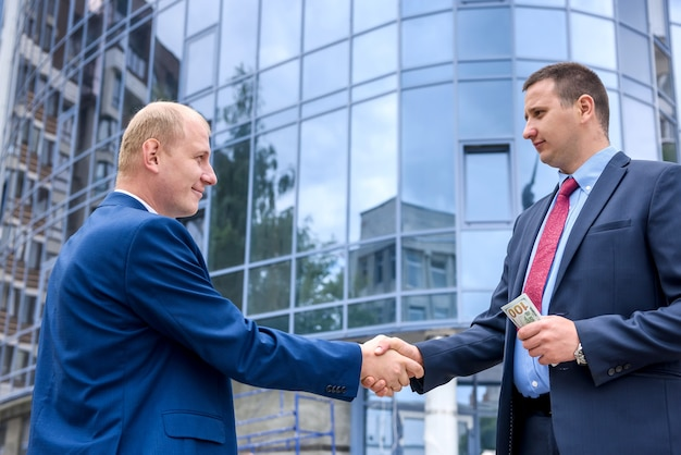 Due uomini d'affari che si stringono la mano prima di un nuovo edificio all'aperto