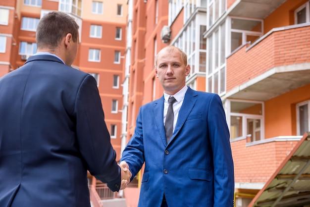 Due uomini d'affari che si stringono la mano vicino al grattacielo all'aperto