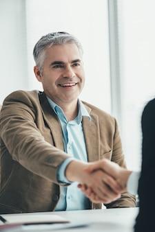 I due uomini d'affari che si stringono la mano in ufficio