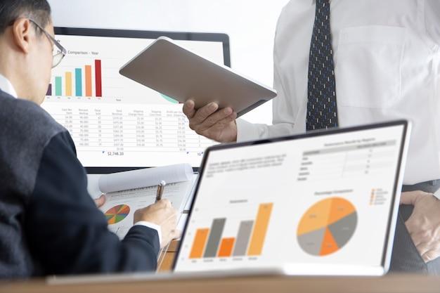Due uomini d'affari in un ufficio moderno che esaminano i rendiconti finanziari sulle prestazioni aziendali e l'analisi del rischio di investimento o il ritorno sull'investimento, roi.