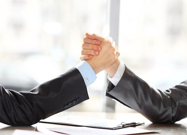 Due uomini d'affari si premono per mano su uno sfondo in avanti