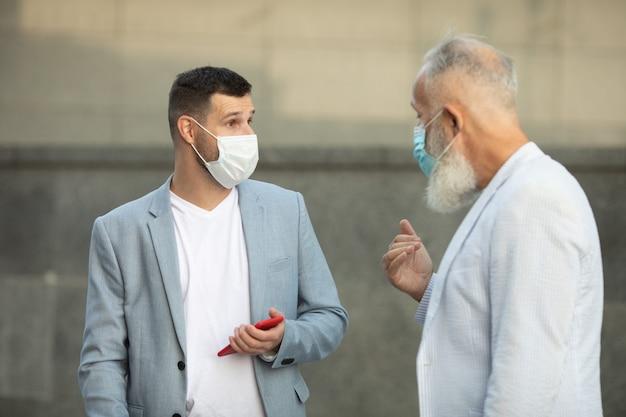 Due uomini d'affari in maschera protettiva discutendo all'esterno dell'edificio per uffici